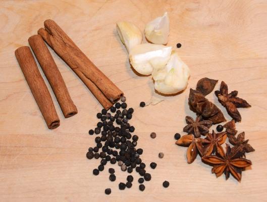 Clockwise from top: cinnamon sticks, fresh garlic, star anise, black peppercorn