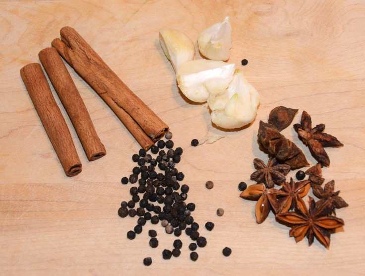Clockwise from top: cinnamon sticks, fresh garlic, star anise, black peppercorn